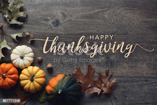 istock Happy Thanksgiving greeting text with pumpkins, squash and leaves over dark wood background 867771348