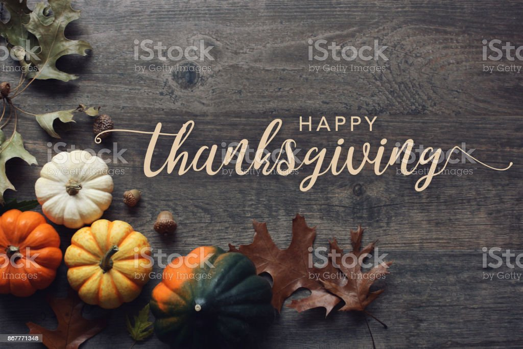 Happy Thanksgiving greeting text with pumpkins, squash and leaves over dark wood background stock photo