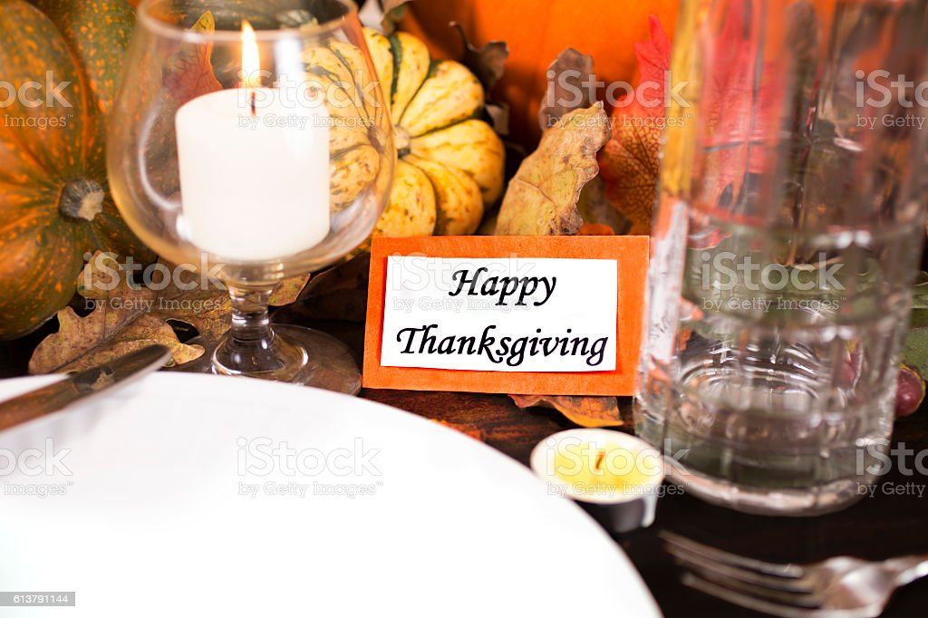 Happy Thanksgiving place setting with autumn centerpiece on dining...