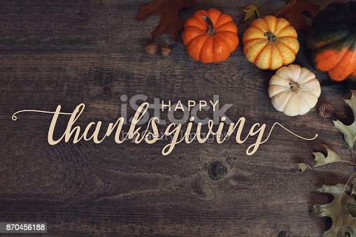 istock Happy Thanksgiving text with pumpkins and leaves over dark wood background 870456188