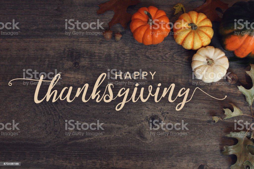 Happy Thanksgiving text with pumpkins and leaves over dark wood background stock photo