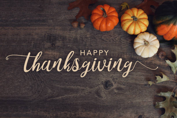 happy thanksgiving text with pumpkins and leaves over dark wood background - thanksgiving стоковые фото и изображения