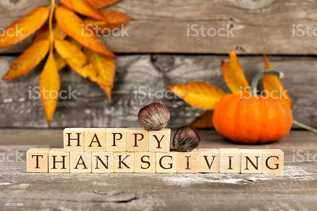 Happy Thanksgiving wooden blocks against rustic wood with autumn leaves stock photo