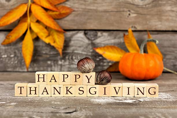happy thanksgiving wooden blocks against rustic wood with autumn leaves - thanksgiving stock photos and pictures