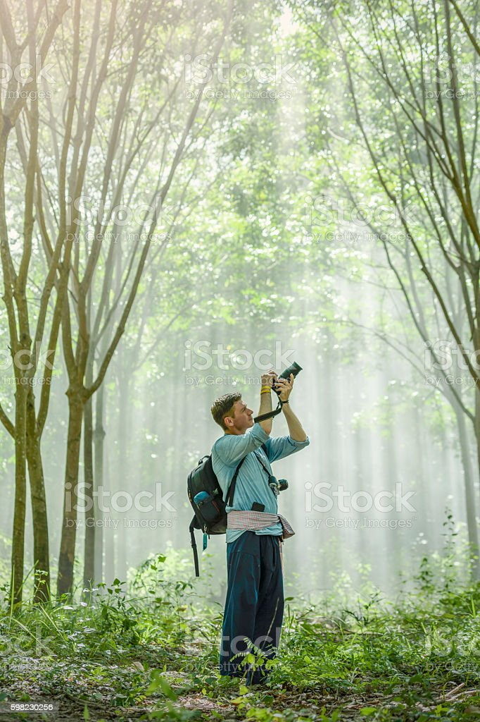 Happy the young man  taking a photo in rubber plantation foto royalty-free