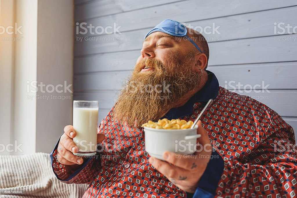 Happy thick guy eating cereals in morning stock photo