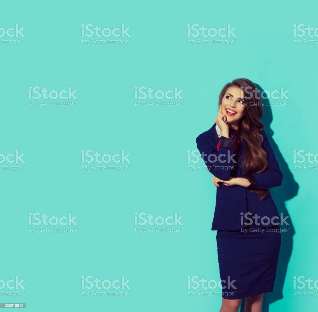 Happy thinking woman looking to the left. Young beautiful hostess stock photo
