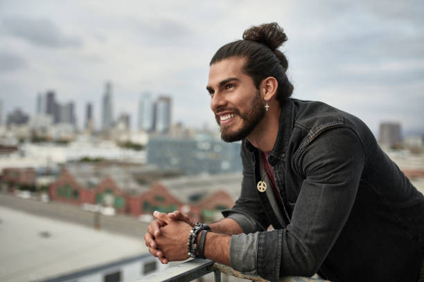 Happy thoughtful man with hands clasped in balcony Smiling thoughtful man standing in balcony. Mid adult male is wearing casuals. He is with hands clasped in city. man bun stock pictures, royalty-free photos & images