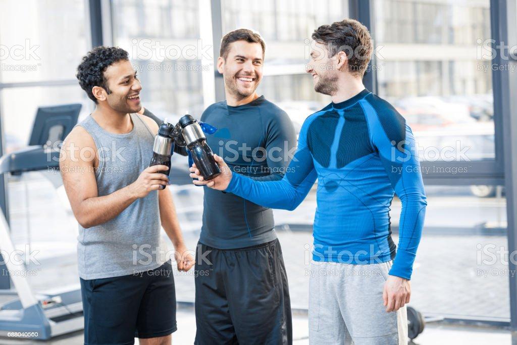Happy three friends at sport club stock photo