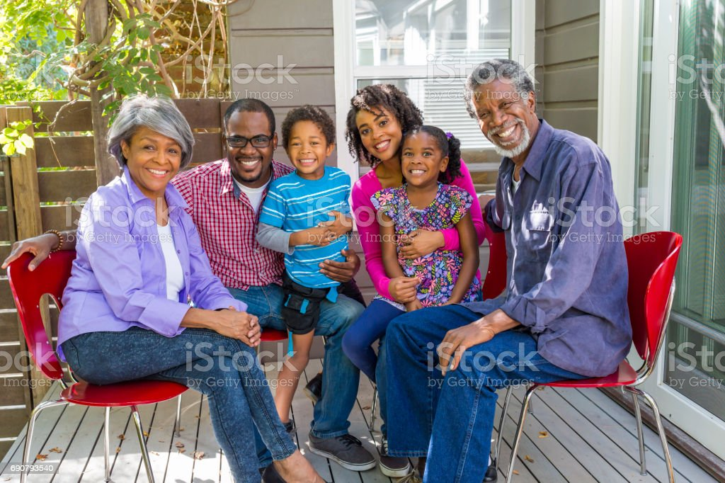 Happy Three Generation African American Family Relaxing at Home stock photo