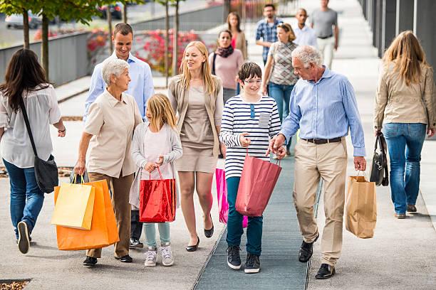 glückliche familie mit drei generationen mit einkaufstüten zu fuß - fußgängerzone stock-fotos und bilder