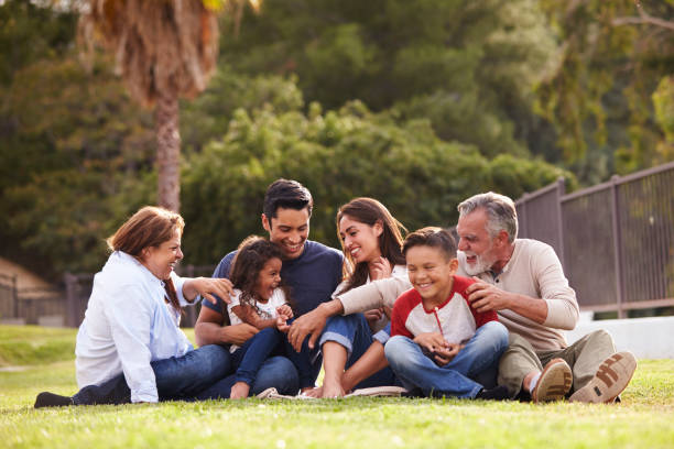 Happy three generation Hispanic family sitting on the grass together in the park, selective focus Happy three generation Hispanic family sitting on the grass together in the park, selective focus monkeybusinessimages stock pictures, royalty-free photos & images