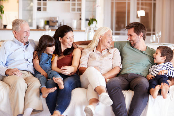 Happy three generation white family sitting on a sofa at home looking at each other, front view stock photo