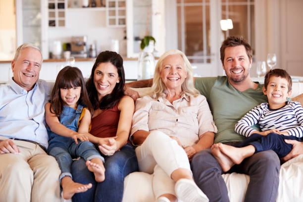 Feliz familia blanca de tres generaciones sentado en un sofá juntos en casa sonriendo a la cámara, vista frontal - foto de stock