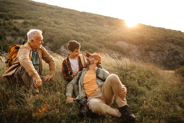 Happy three generations males relaxing on hiking tour stock photo