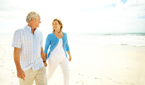 Happy times together A happy senior couple walking on the beach holding hands land feature stock pictures, royalty-free photos & images