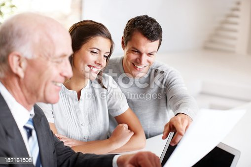 Smiling young couple going over a document with a financial advisor