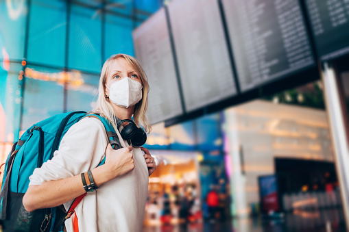 Portrait of a young woman checks the arrivals and departures board at the airport. She wears a face mask for protection during a Coronavirus pandemic. New normal lifestyle for public transport after Covid-19