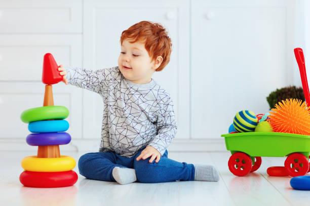 glücklich kleinkind baby boy sortierung bunte ringe auf pyramide - pyramide sammlung stock-fotos und bilder