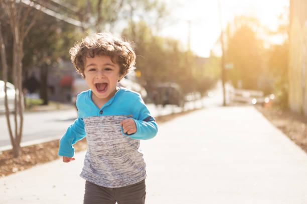 Happy Toddler Boy Running Down the Sidewalk stock photo