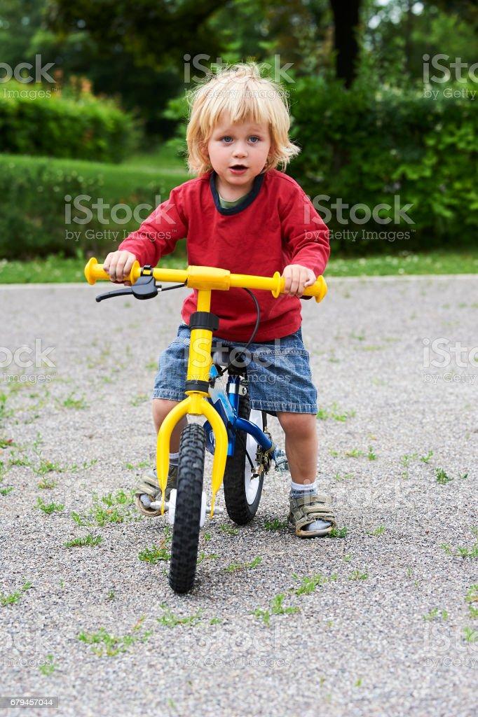 Happy toddler child boy riding bike. Kids enjoying a bicycle ride. royalty-free stock photo