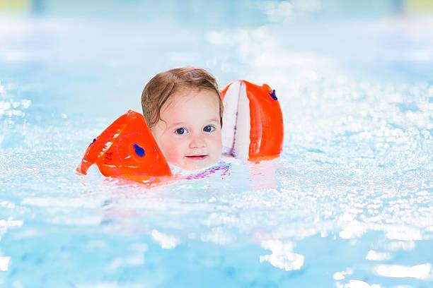 glücklich kleinkind mädchen spaß im pool - armband water stock-fotos und bilder