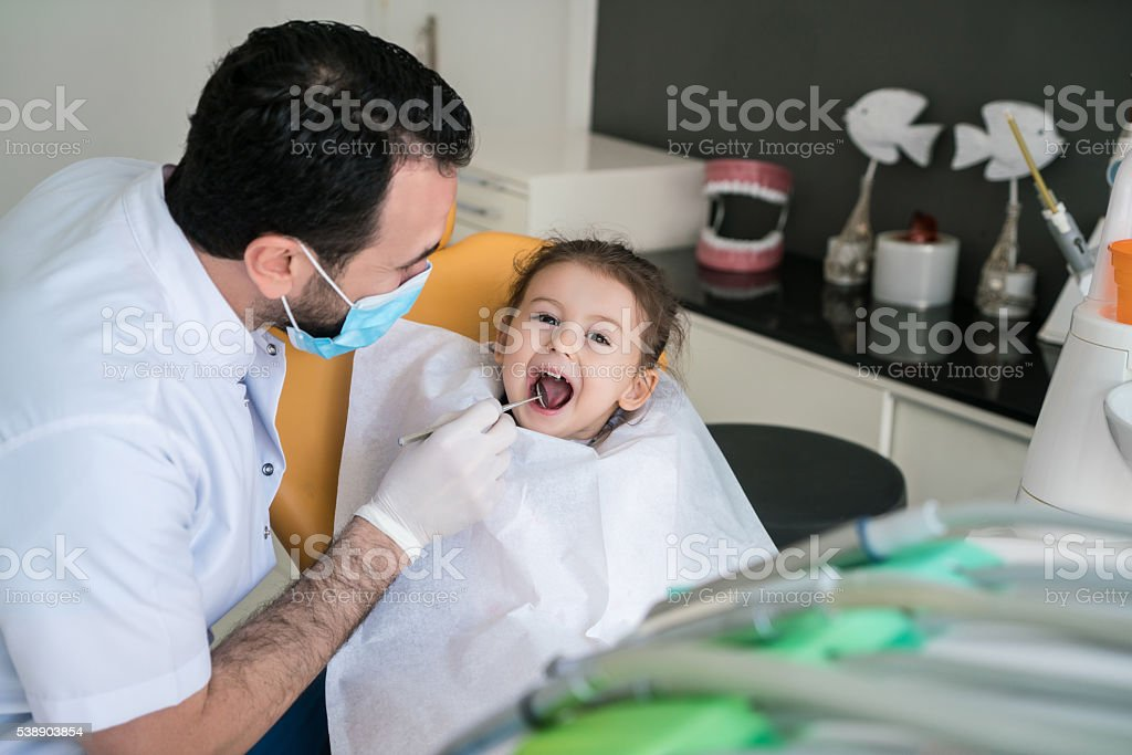 Happy toddler girl having her teeth examined at dentist office. stock photo