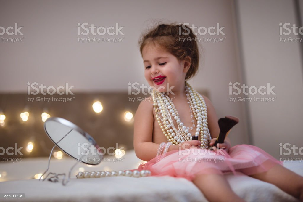 Happy toddler girl imitating adults stock photo
