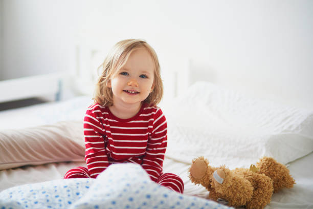 Happy toddler girl in striped red and white pajamas sitting on bed stock photo