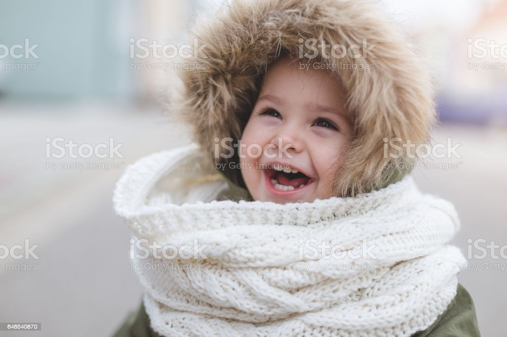Happy toddler girl laughing - winter fashion stock photo