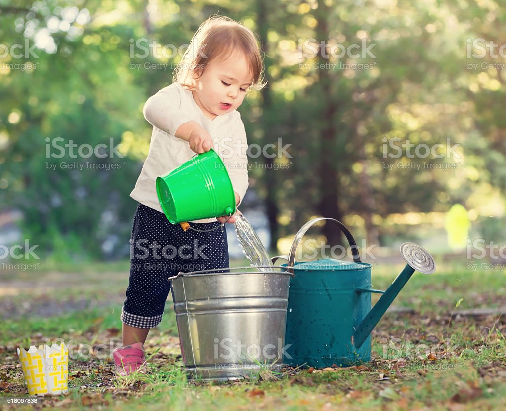 Happy toddler girl playing outside stock photo