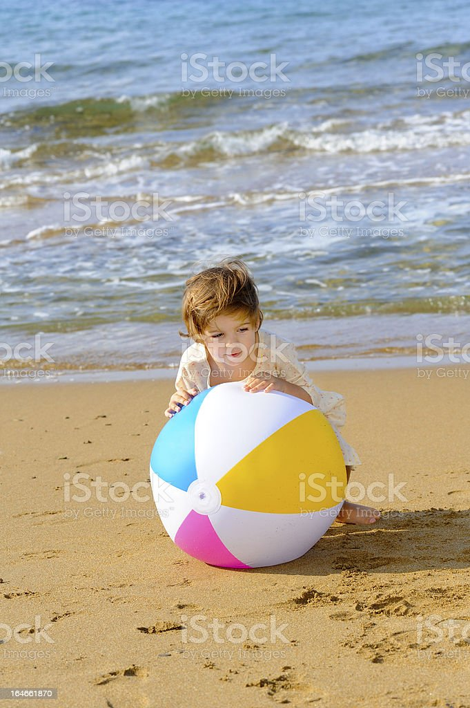Happy toddler girl playing with her colorful ball at beach royalty-free stock photo