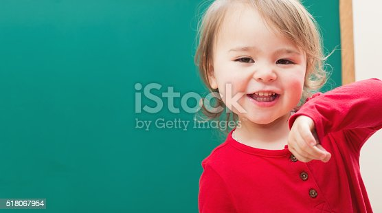 istock Happy toddler girl smiling in front of a chalkboard 518067954