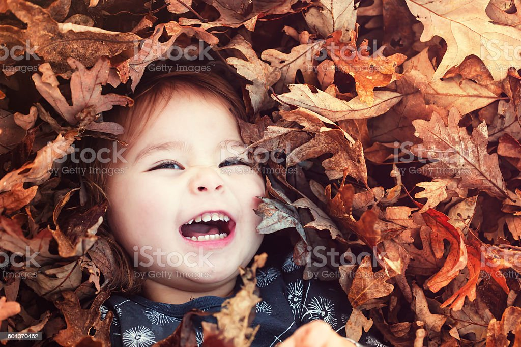 Happy toddler girl smiling while lying down in a pile – Foto