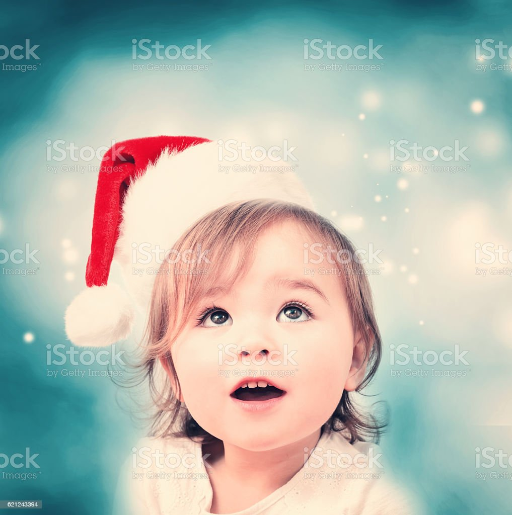 Happy toddler girl with Santa hat stock photo
