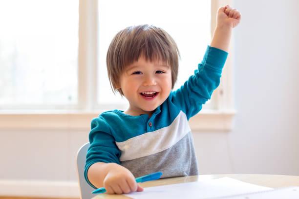 gelukkige peuter die zijn hand opheft - jongensbaby's stockfoto's en -beelden