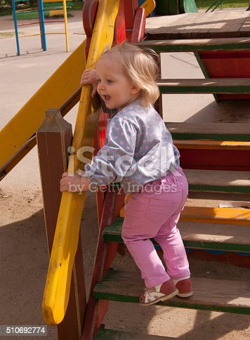 656743520 istock photo Happy toddler shouting on the wooden slide steps 510692774