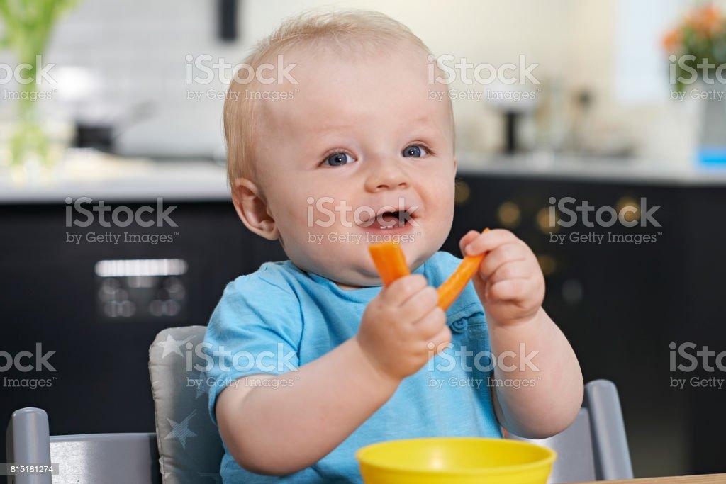 Niño feliz sentado en la mesa comiendo zanahorias frescas - Foto de stock de Alegre libre de derechos