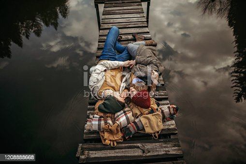 Hipster couple laying down on dock over the lake