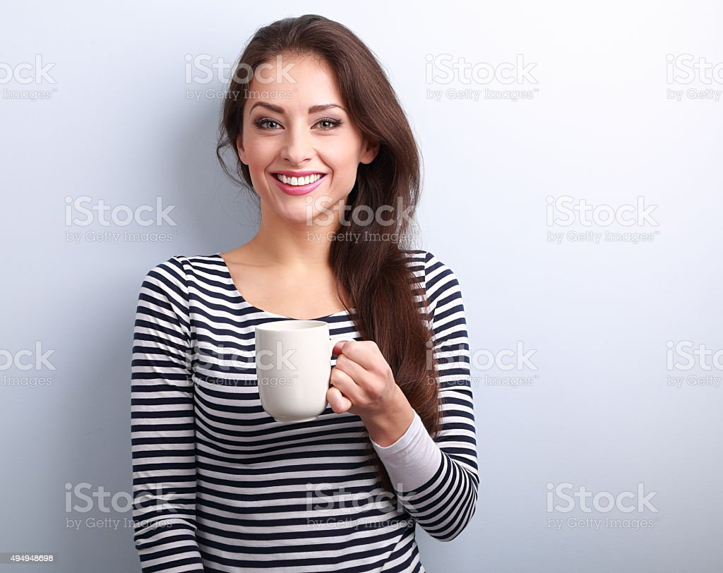 Happy toothy smiling casual young woman with cup of tea stock photo