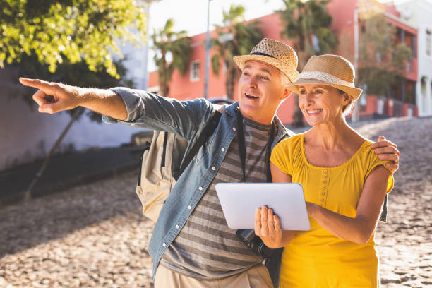 Happy tourist couple using tablet pc in the city stock photo