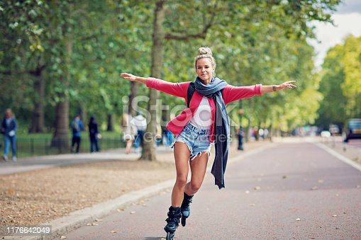 Happy tourist girl is skating on the street
