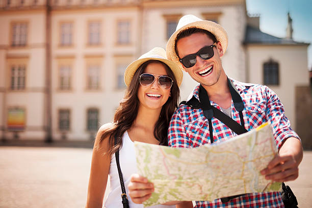 happy tourists couple holding map - tourism stock pictures, royalty-free photos & images