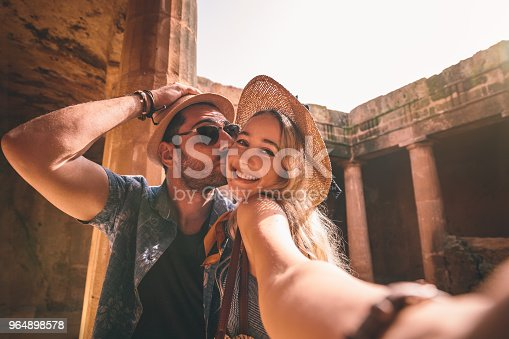 Tourists couple taking selfies while doing sightseeing at ancient monument with stone columns in Europe