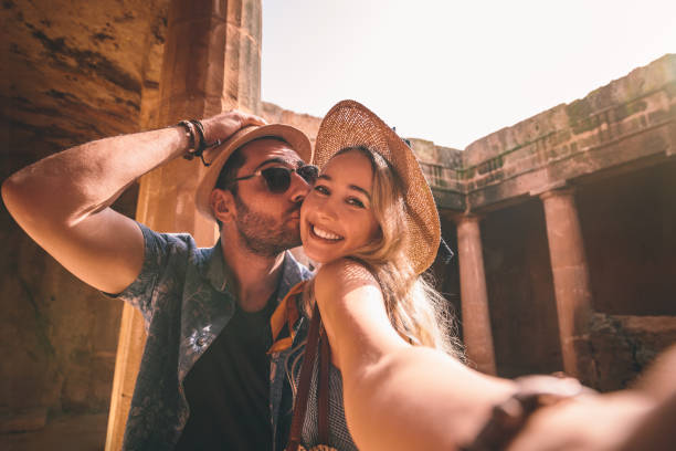 Happy tourists couple taking selfies on summer holidays in Greece Tourists couple taking selfies while doing sightseeing at ancient monument with stone columns in Europe honeymoon stock pictures, royalty-free photos & images