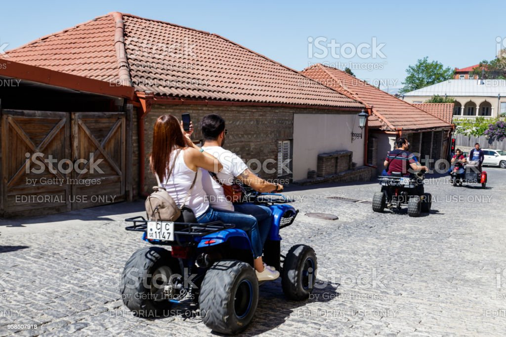 Happy tourists riding all terrain vehicle on street of the medieval town Sighnaghi stock photo