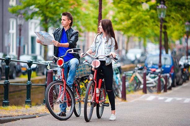 glückliche touristen sehenswürdigkeiten stadt mit karte auf fahrräder - hochzeitsreise amsterdam stock-fotos und bilder
