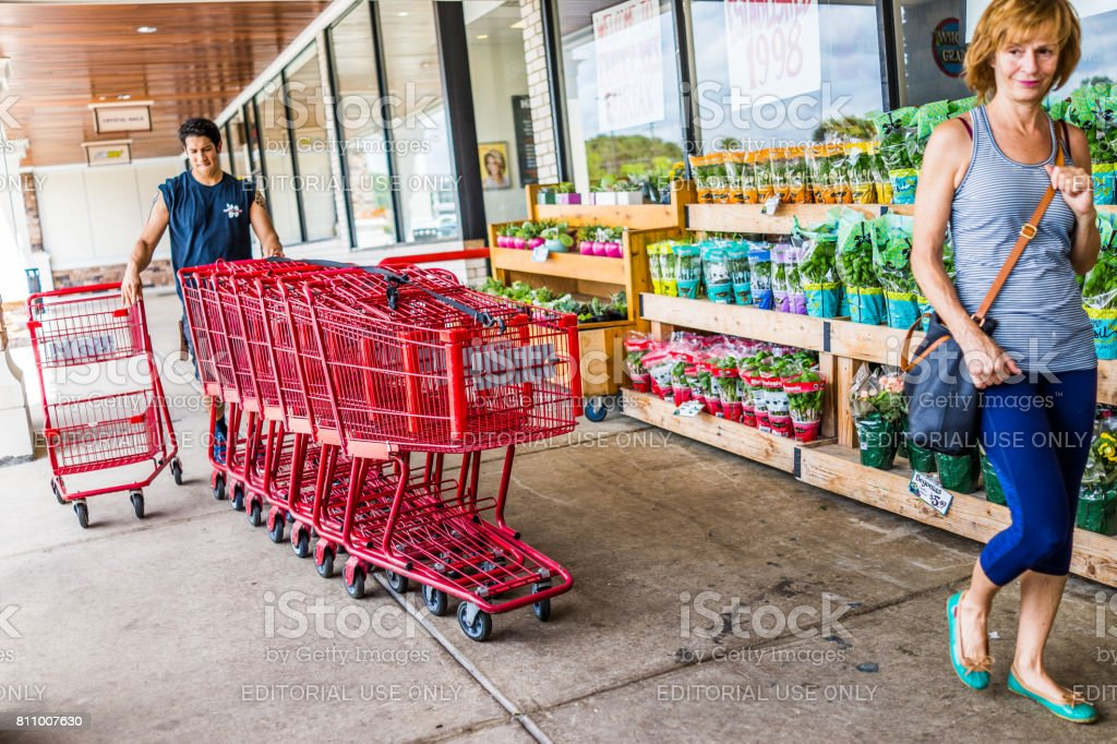 Happy Trader Joe's employee returning shopping carts to the store outside entrance with woman customer stock photo
