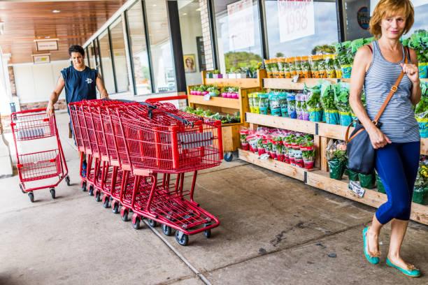 glücklich trader joes mitarbeiter wieder einkaufswagen in den laden vor eingang mit frau kunde - aldi karriere stock-fotos und bilder