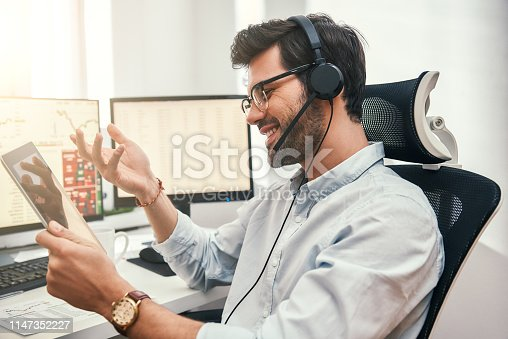 istock Happy trader. Successful bearded businessman in headset holding digital tablet, talking with client and smiling while sitting in front of monitor screens in the office. 1147352227